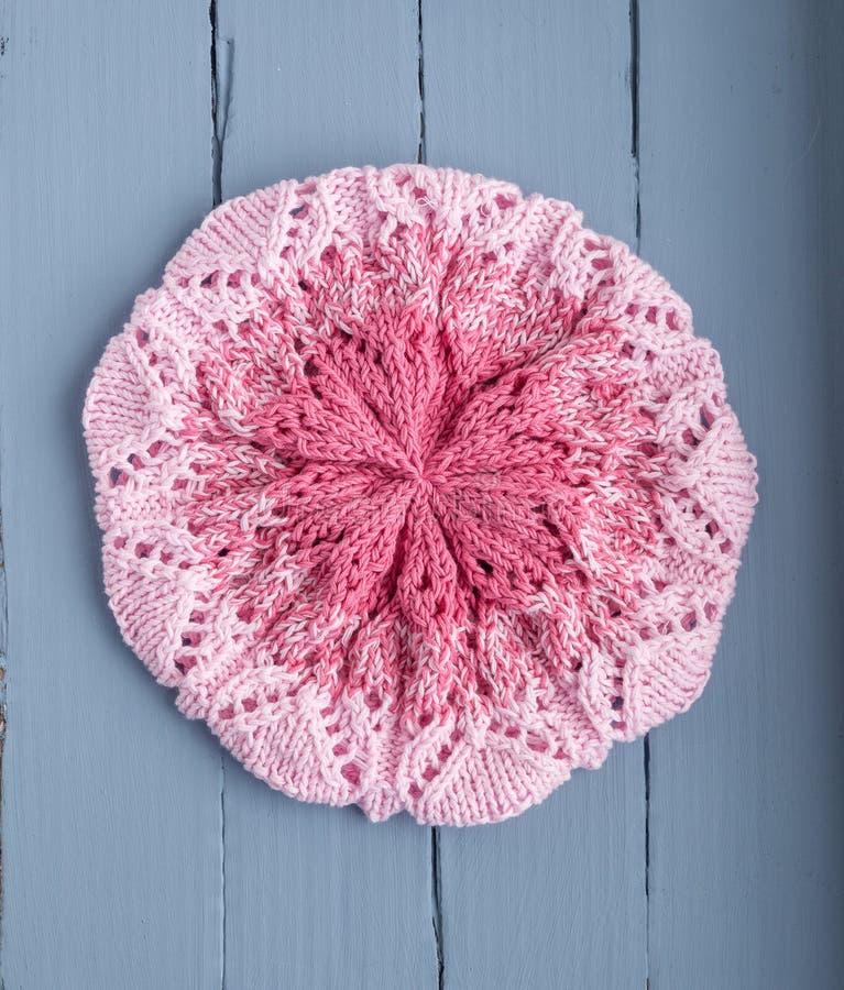 Béret rose à jour tricoté pour des femmes sur un fond bleu photographie stock