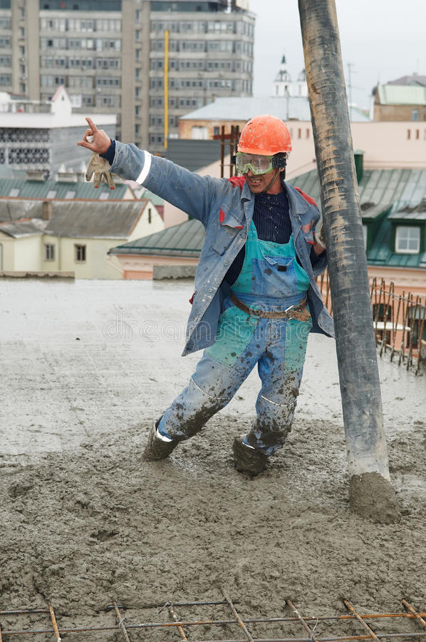Béton se renversant d'ouvrier de constructeur photo libre de droits