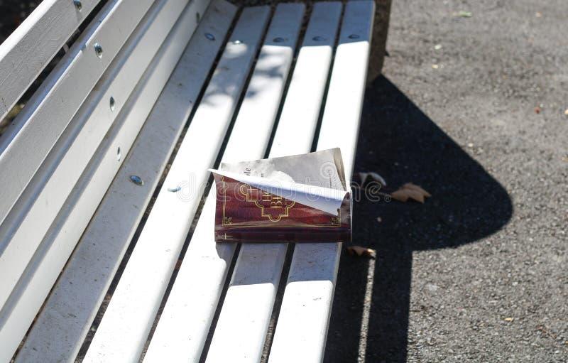 A Bíblia abandonada em um banco imagens de stock royalty free
