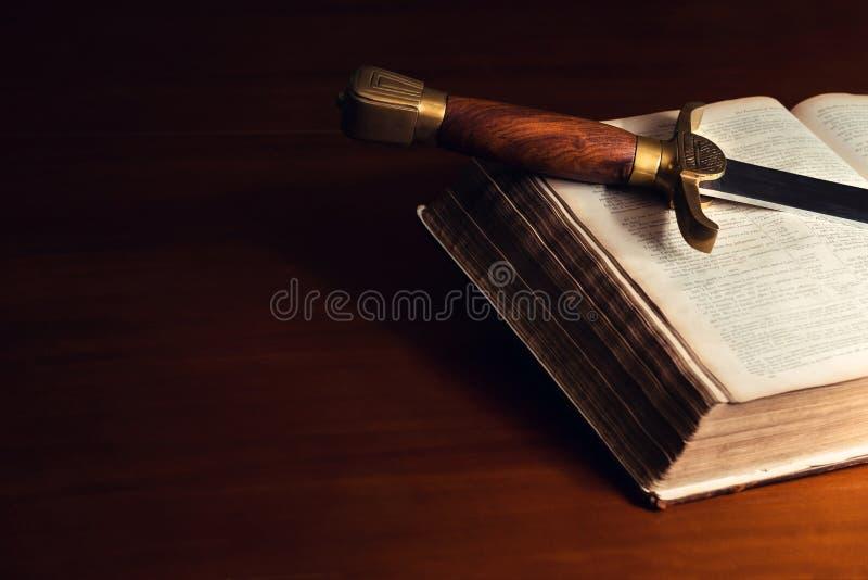 A Bíblia aberta velha com espada fotografia de stock