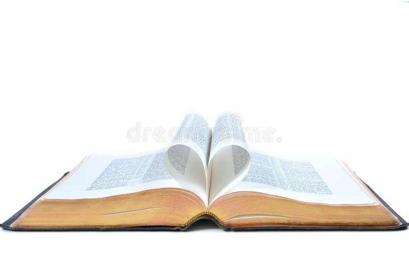 A Bíblia completa com o coração que forma das páginas abertas imagens de stock