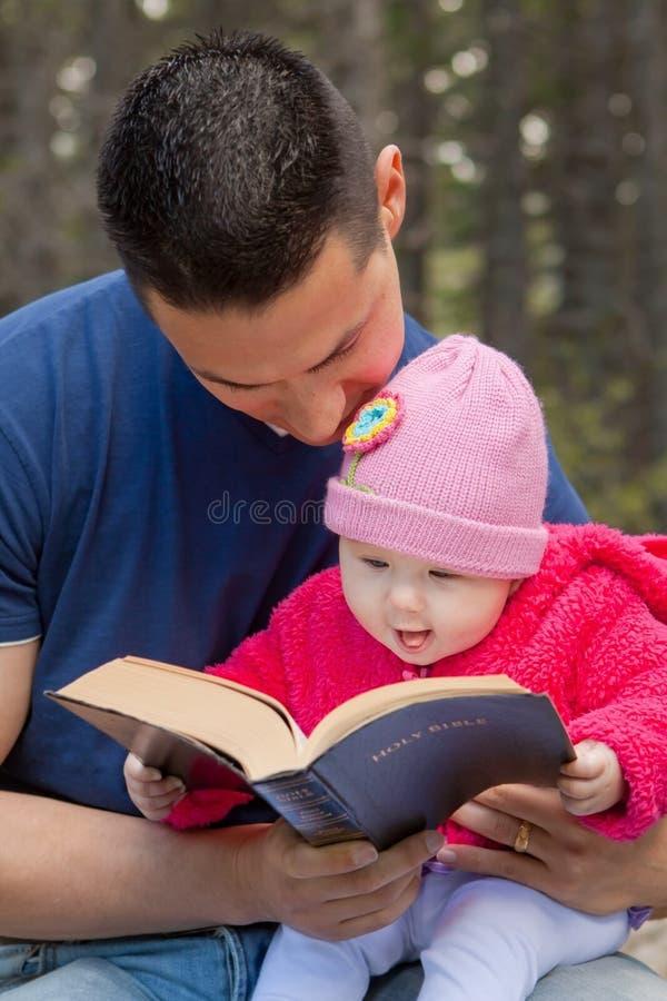 A Bíblia da leitura da filha do paizinho e do bebê imagens de stock