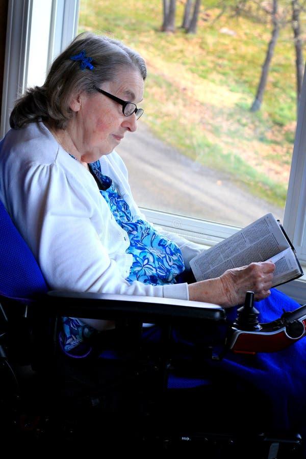 A Bíblia da leitura da mulher de Handycapped imagens de stock