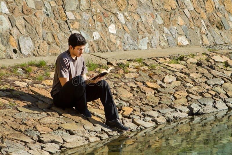 A Bíblia da leitura do homem pelo lago foto de stock royalty free