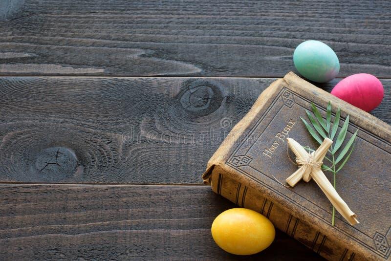 A Bíblia de couro do vintage com cruz da grama, folhas de palmeira, ovos da páscoa coloridos na placa de madeira rústica escura imagens de stock