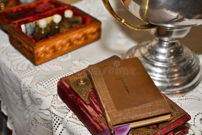 A Bíblia encontra-se na tabela com o copo na igreja antes do rito do batismo foto de stock