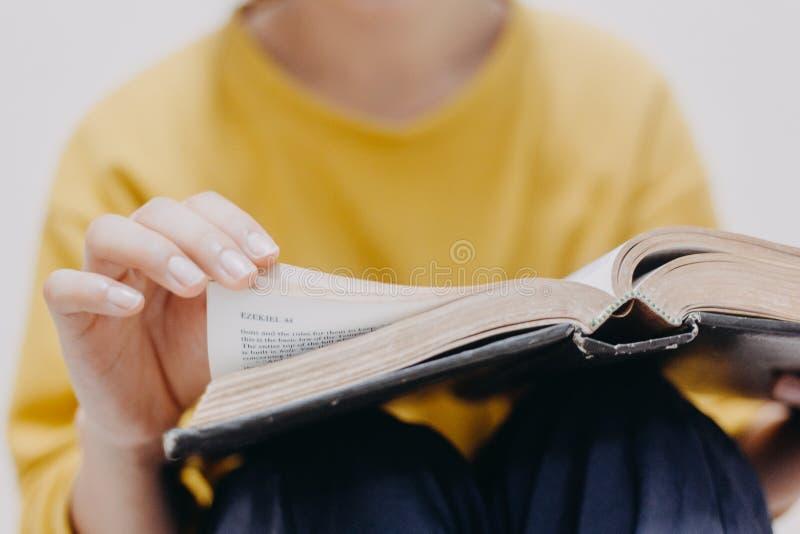 A Bíblia Sagrada aberta da mulher das mãos fotos de stock
