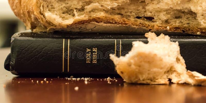 A Bíblia Sagrada com o naco de pão na parte superior e de migalha na parte dianteira fotos de stock royalty free
