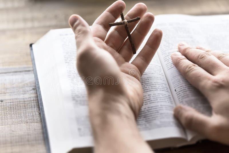 A Bíblia Sagrada da leitura que mantém uma cruz de madeira disponivel imagem de stock
