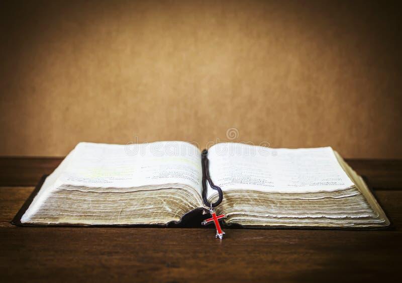 A Bíblia Sagrada e o vermelhos cruzam-se sobre na tabela de madeira imagens de stock royalty free