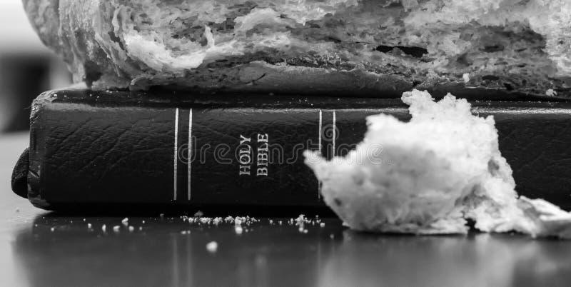 A Bíblia Sagrada preto e branco com o naco de pão na parte superior e de migalha na parte dianteira imagem de stock