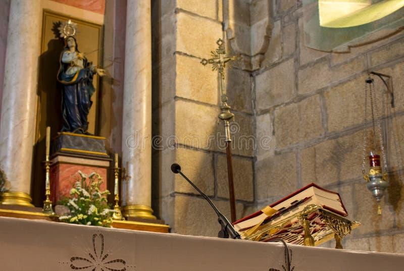 A Bíblia vermelha na tabela do altar com escultura do microfone e do Saint Conceito da fé e da religião Interior do altar da igre fotografia de stock