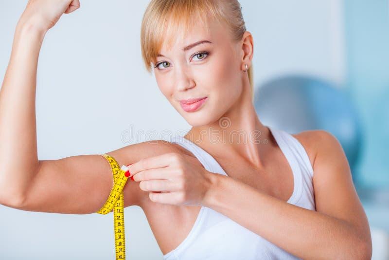 Bíceps de medição da mulher loura foto de stock