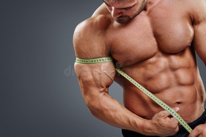Bíceps de medición del culturista con cinta métrica fotos de archivo libres de regalías