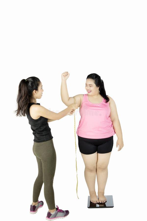 Bíceps de medición del instructor de la mujer gorda imagenes de archivo
