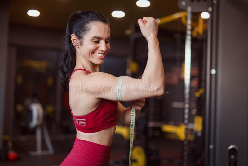 Bíceps de medición sonriente de la mujer fotografía de archivo libre de regalías