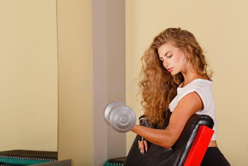 Bíceps del ejercicio de la muchacha con los pesos de la mano foto de archivo libre de regalías