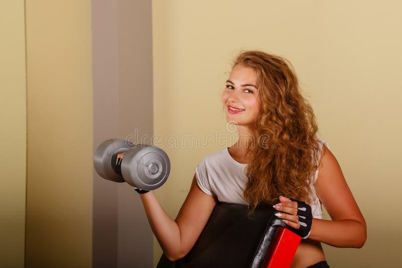 Bíceps del ejercicio de la muchacha con pesa de gimnasia foto de archivo