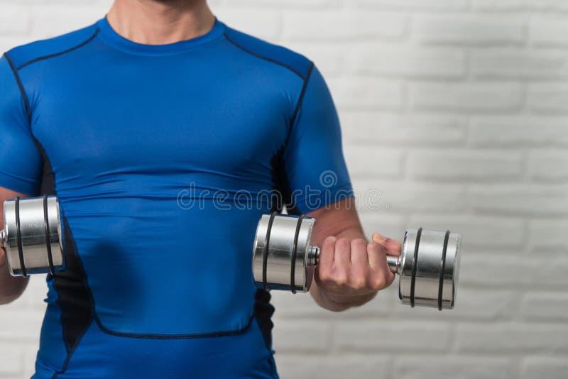 Bíceps del ejercicio del hombre del primer con pesas de gimnasia imagenes de archivo