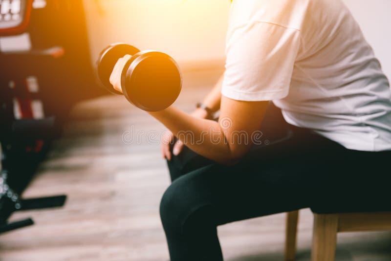 Bíceps do treinamento do peso da mulher do close up no clube de esporte imagem de stock royalty free