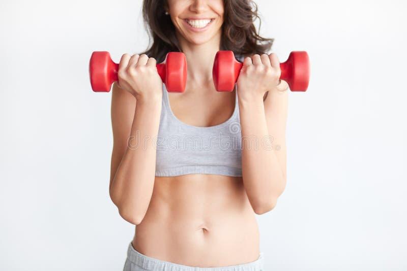 Bíceps emocionado del entrenamiento de la mujer con pesas de gimnasia imagen de archivo libre de regalías