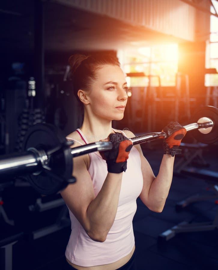 Bíceps hermoso joven del entrenamiento de la mujer con el barbell foto de archivo