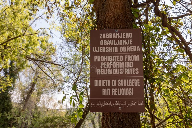 Bósnia e Herzegovina, em abril de 2019: Sinal pela cachoeira de Kravice: Proibido de executar ritos religiosos fotos de stock