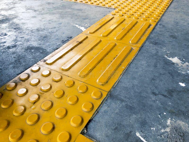 Bóveda y bloque amarillos de pavimentación táctil que actúan como dirección para que el ciudadano con deficiencias visuales o cie imagen de archivo libre de regalías
