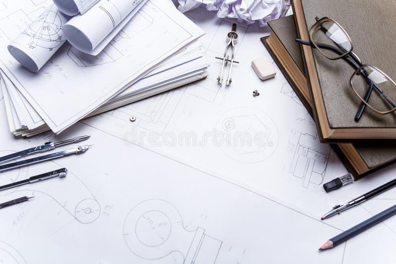 Böcker, exponeringsglas, blyertspenna, kompass och rullar av teckningar på detaljerna av industriella teckningar royaltyfri bild