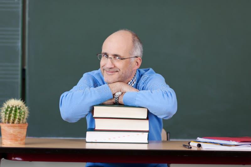 Böcker för professor Relaxing On Stacked på skrivbordet arkivbild