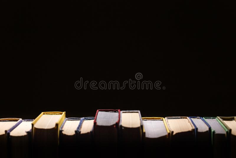 Böcker i arkiv på svart bakgrund med Kopia-utrymme Begrepp av utbildning och kunskap royaltyfri foto