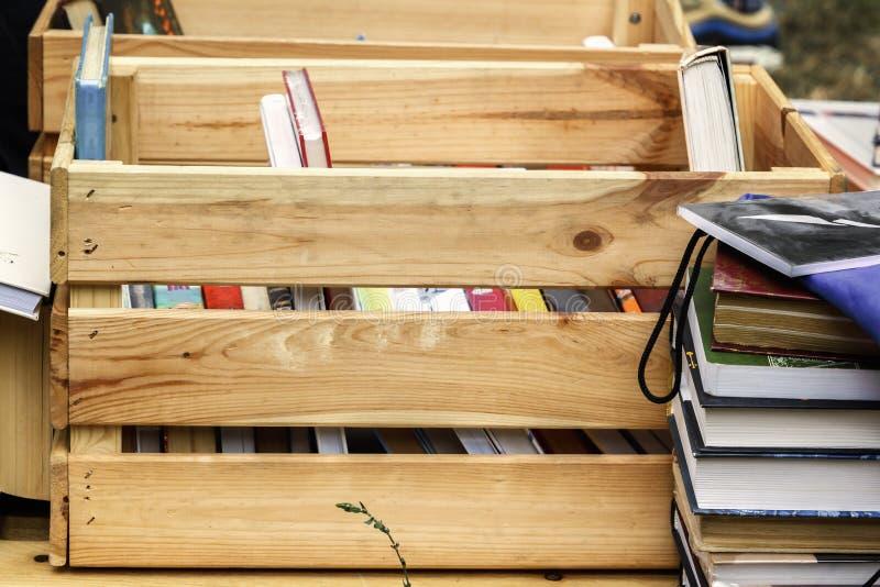 Böcker i en träask är förberett till salu på en gatamässa royaltyfri fotografi