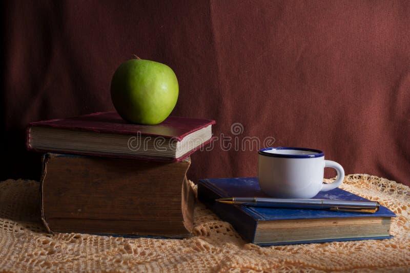 Böcker med äpple- och kaffekoppen. arkivbild