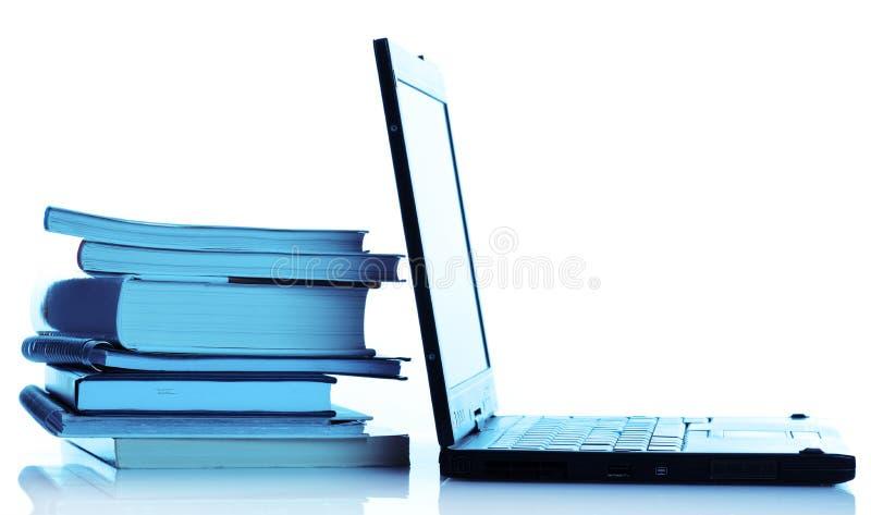 Böcker med bärbar dator fotografering för bildbyråer