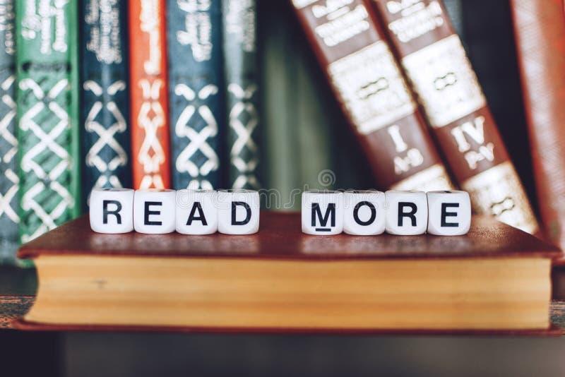 Böcker på hyllan med ord som MER LÄS Text LÄSTE MER på boken Läsa och att lära, utbildning, arkivbegrepp arkivbild