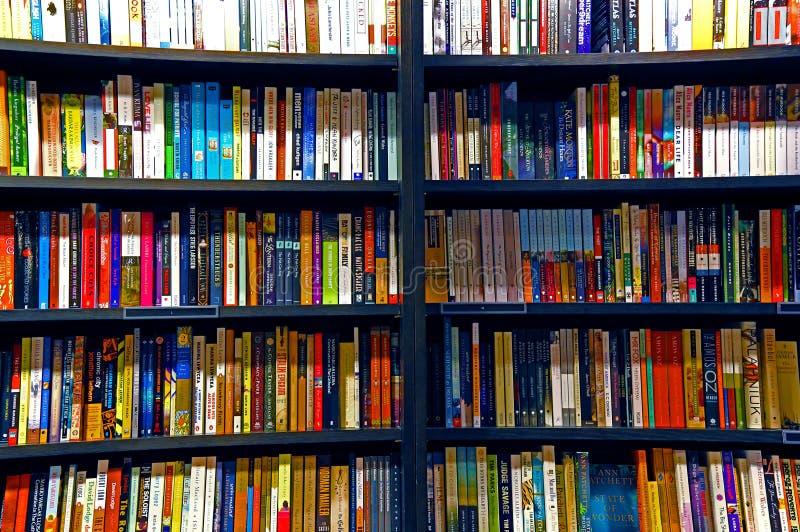 Böcker på hyllor arkivfoton