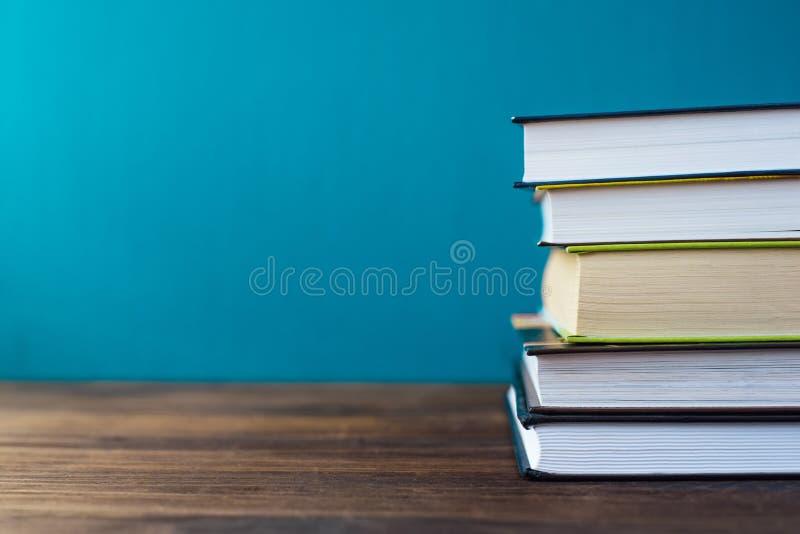 Böcker på tabellen framme av kritabrädet royaltyfria bilder