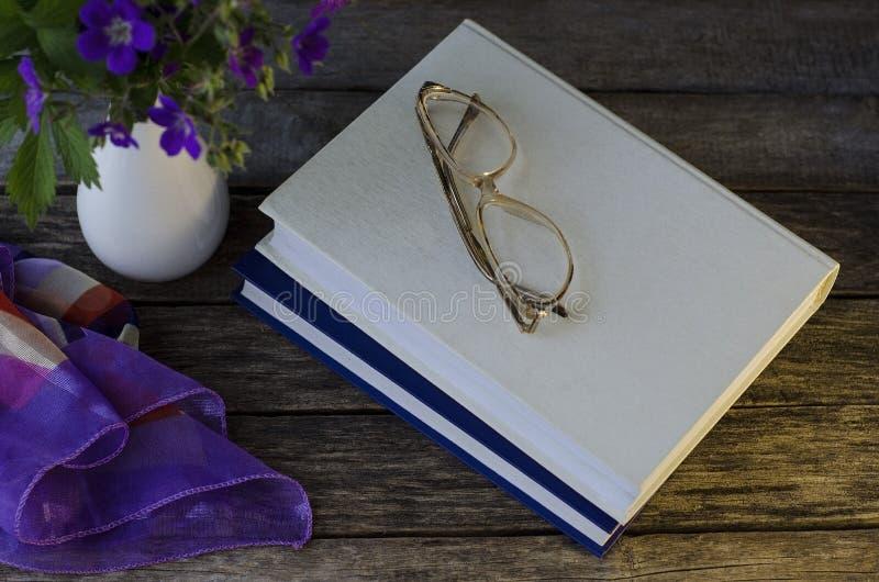 Böcker på tabellen med exponeringsglas Aftonl?sning royaltyfri fotografi