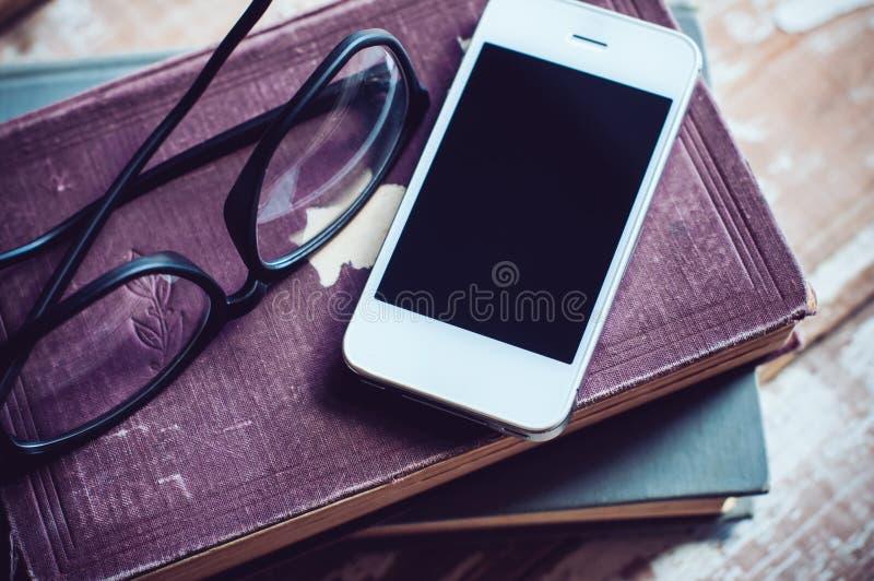 Böcker, smartphone och exponeringsglas royaltyfri fotografi