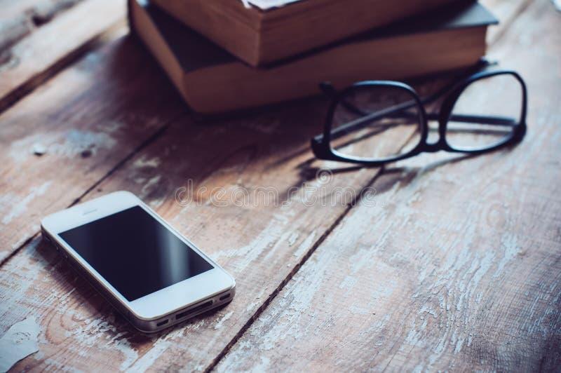 Böcker, smartphone och exponeringsglas royaltyfria foton