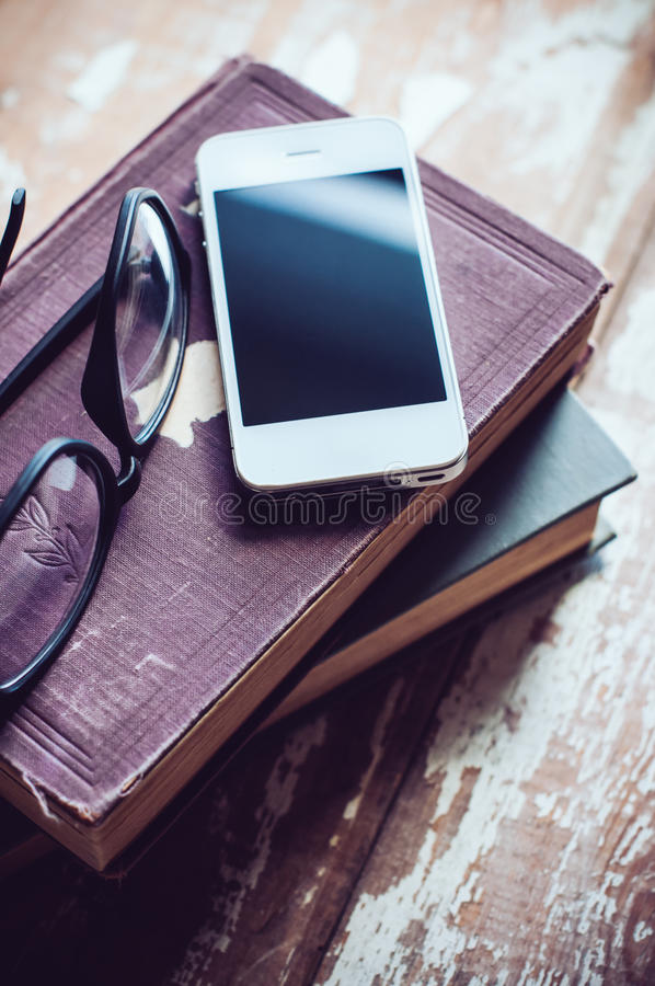 Böcker, smartphone och exponeringsglas royaltyfria bilder