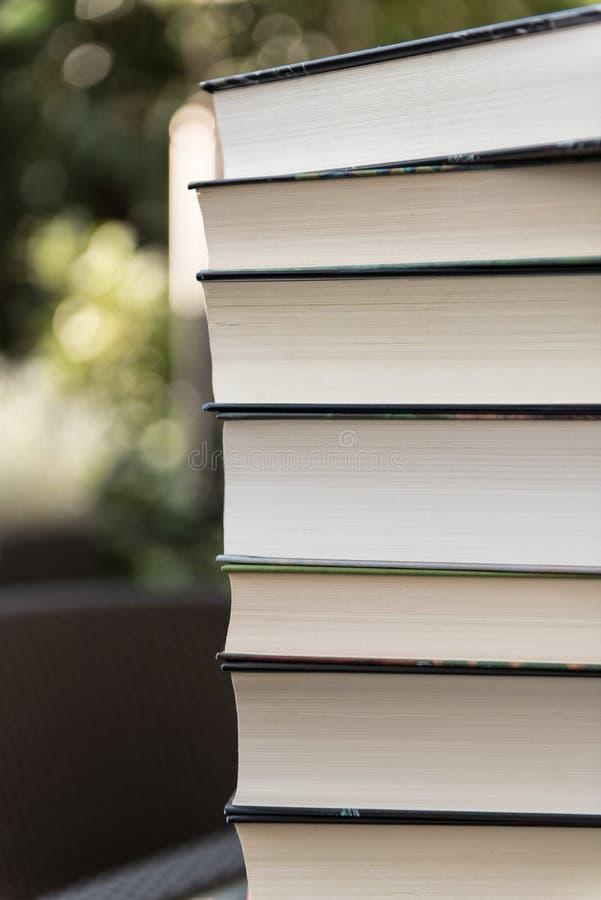 Böcker som staplas på den trädgårds- tabellen arkivbild