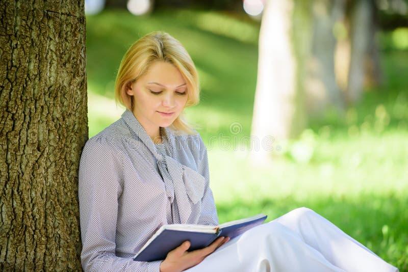 Böcker som varje flicka bör läsa Den koncentrerade flickan sitter parkerar läst boknaturbakgrund Läsa inspirera böcker kvinnlig royaltyfri fotografi