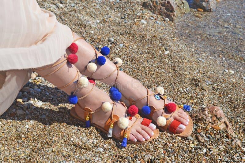 Böhmische griechische Sandalen mit bunter pom pom Anzeige auf dem Strand lizenzfreie stockbilder
