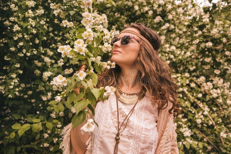Böhmische junge Frau, die Blumenduft genießt lizenzfreie stockfotos