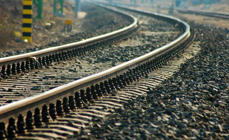 Böjande järnväg med hundratals kiselstenar, bredvid den arkivfoto