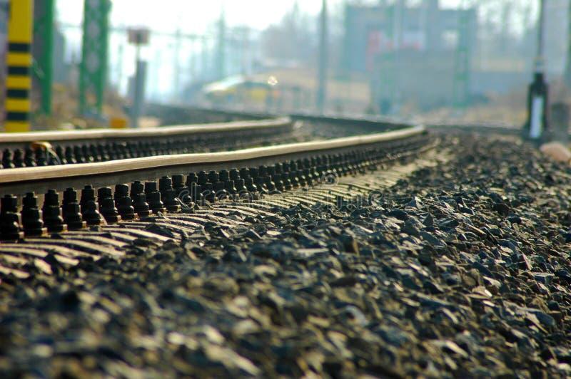 Böjande järnväg med hundratals kiselstenar royaltyfria bilder