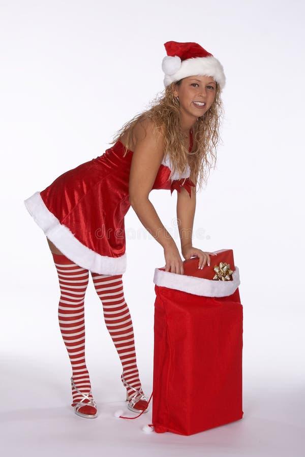 böjande klänninggåva för påse över röda avrivna santa strumpor royaltyfri fotografi