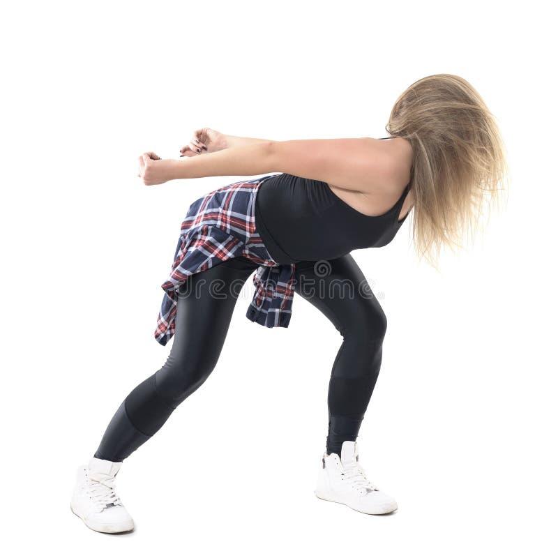 Böjde poserar kvinnlig dansareflyttning för dancehall och lyftahuvudet med flödande hårrörelse fotografering för bildbyråer