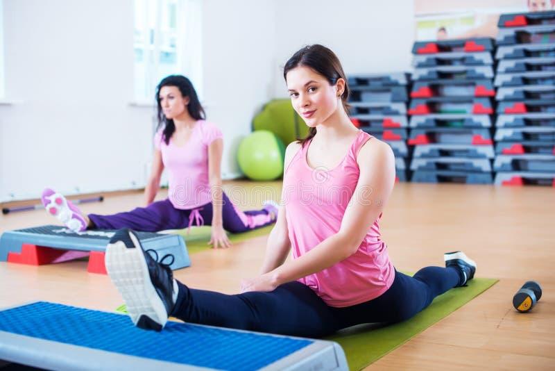 Böjliga passformkvinnor som sträcker ben med aerobiska momentplattformar arkivbild